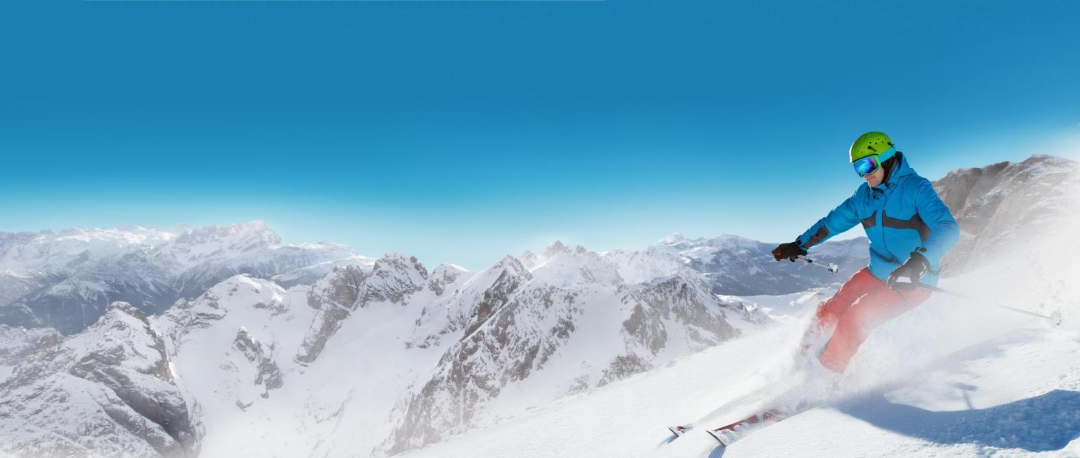 Man skier running downhill on sunny alpine slope in Beaver Creek