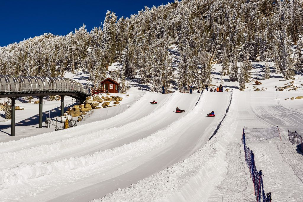 Tourists tubing on the slopes of Heavenly Ski Resort on a sunny winter day