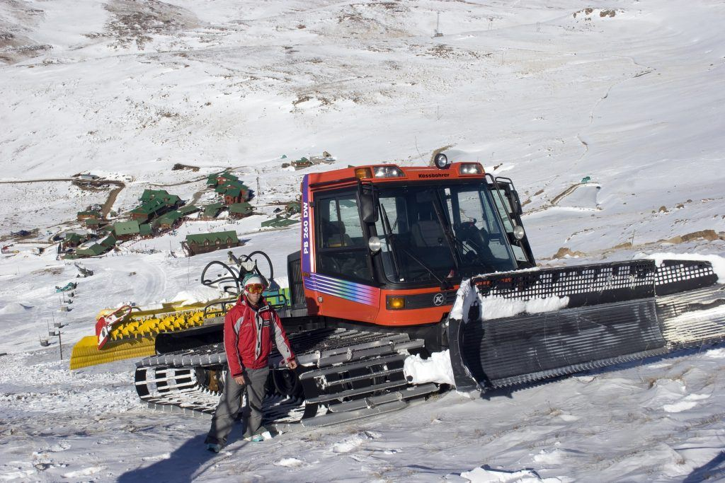 A man stands next to his slope groomer at the top of the slope at Tiffendell, South Africa.