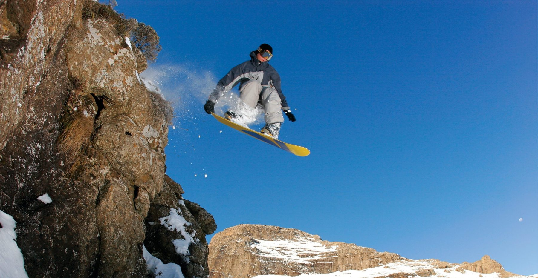 A snowboarder jumps off a cliff in rural Lesotho.