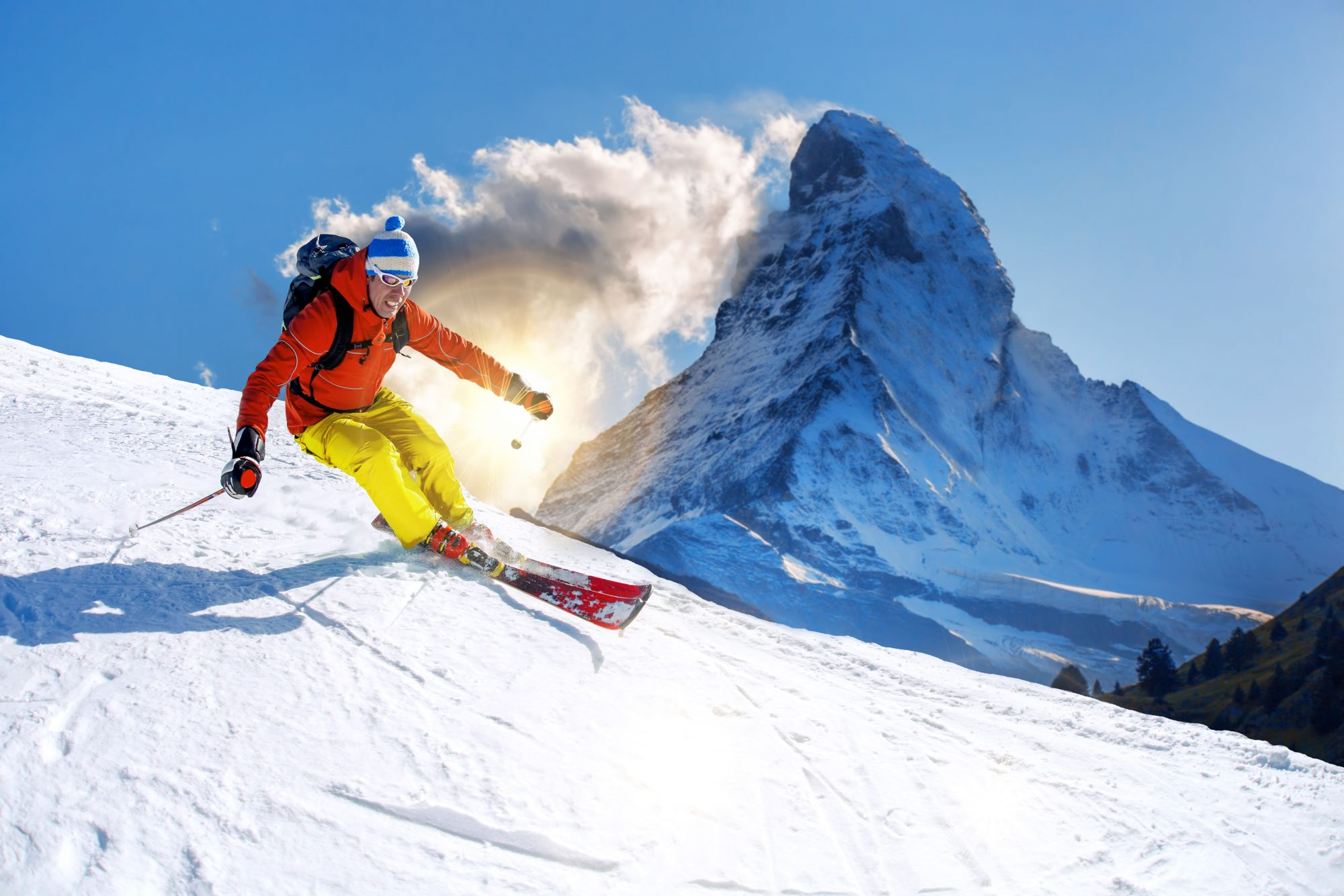 Skier going downhill, with Matterhorn in the background.
